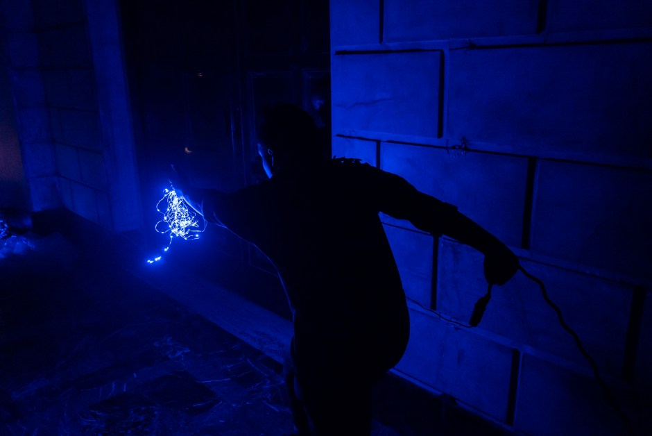 alt text: Photo of Shantelle Courvoisier lunging forward in the dark ISSUE Project Room space, holding a blue string light in her left hand and a wire in her right hand.