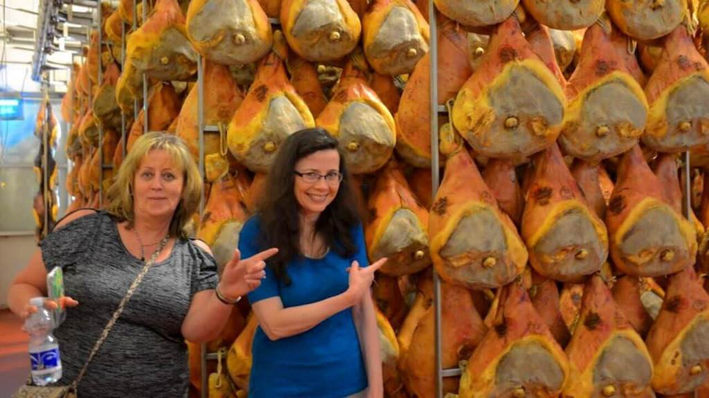 a wall of prosciutto aging in Parma