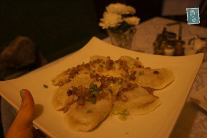 A plate of pierogi with fried onion