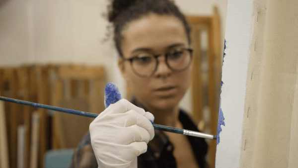 A young woman holds a paintbrush to a canvas