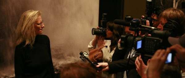 Annie Leibovitz on the left in front of a black a large black and white photo standing in front of a crowd of reporters and news cameras.