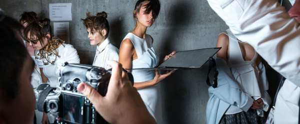 A group of female models pose against a cement wall, one holds a reflector as she is posing while a photographer captures her in the foreground and a person holds a light in the right of the frame, their arm covering the right corner of the photo.