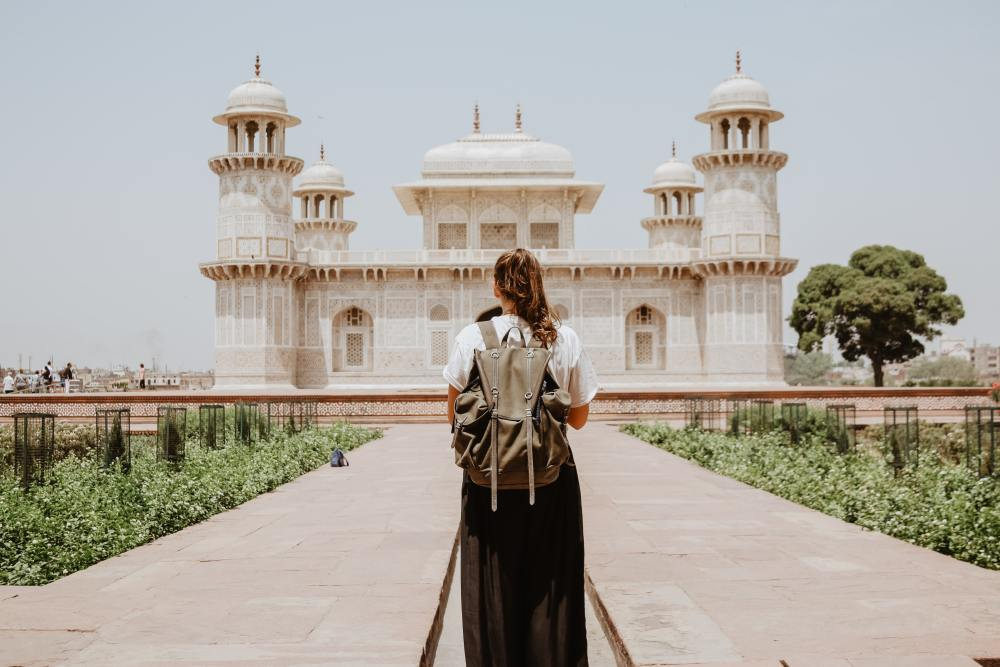 image of women standing in front of Taj Mahal. Meant to demonstrate feeling small in face of culture