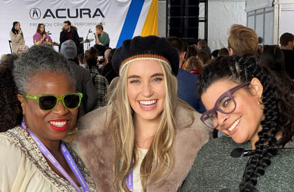 Three women smiling in front of stage