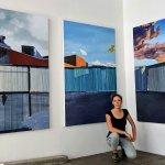 Christine Rasmussen kneels in front of her paintings titled The Glow (it wasn't from a phone), Parts I, II, & III. Oil on canvas over panel. 72 x 144 inches. The paintings are of a corrugated metal fence along a skyline with buildings behind, pink and white clouds, and mountains.