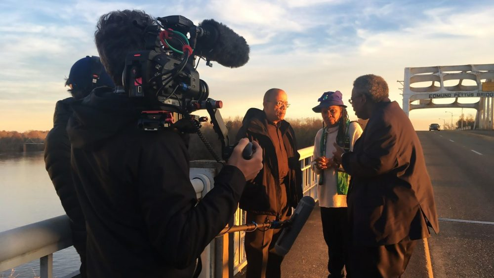 Camera crew interviewing three Black people on the Edmund Pettus Bridge.