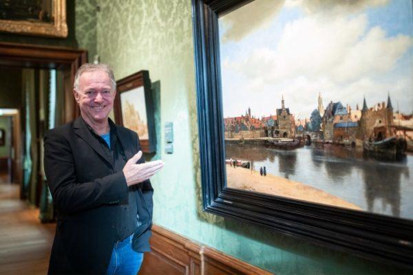 Harry Jeckers in het Mauritshuis naast ''Gezicht op Delft'' van Johannes Vermeer