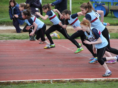 Photo of young people starting a race on an athletics track