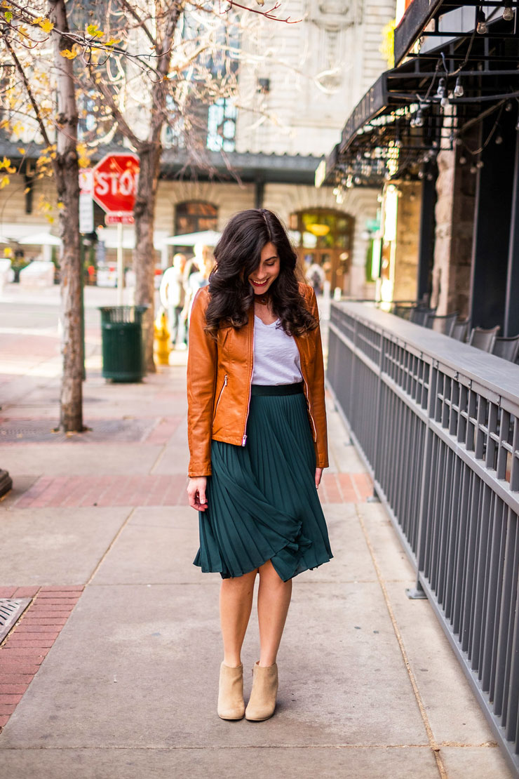 forest green pleated skirt with a tan faux leather jacket for date night www