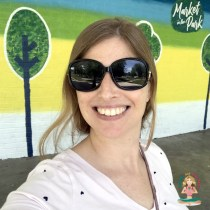 Author Angela outside by a mural with trees