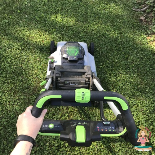 close up of a hand pushing a lawn mower over green grass