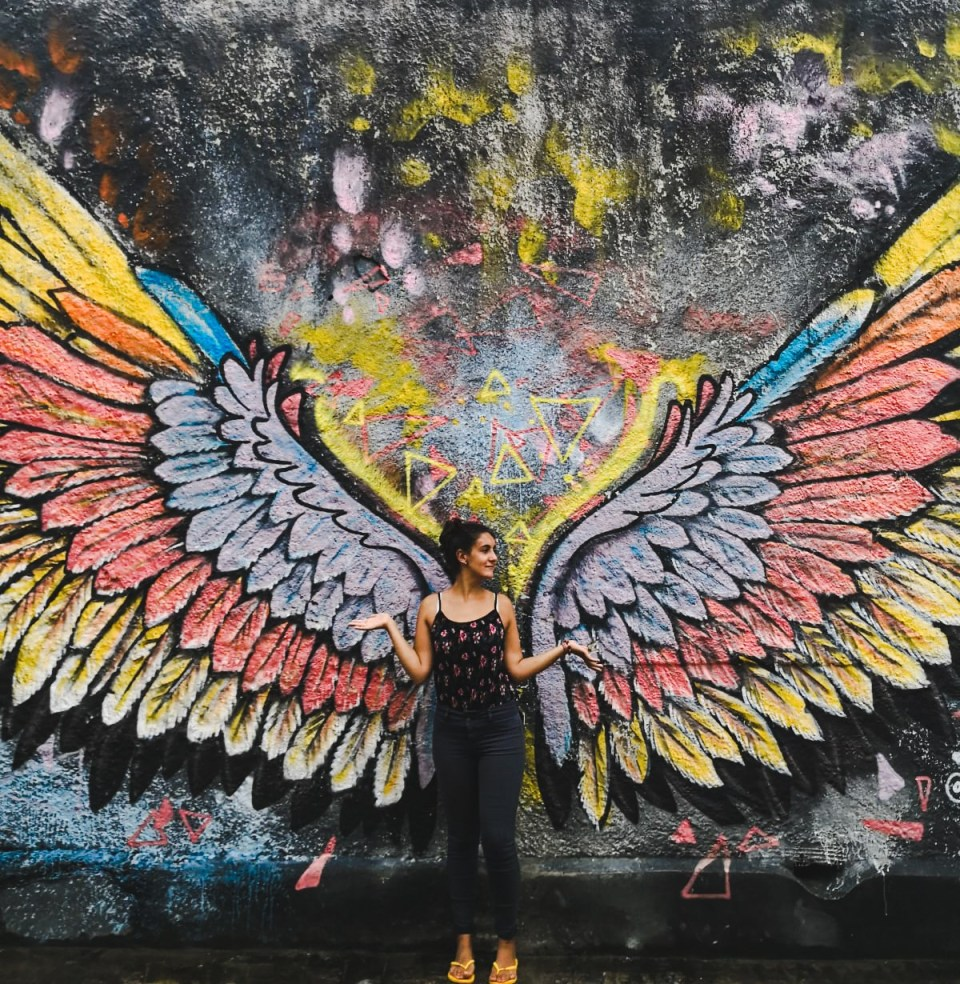 backpacker girl next to wing mural: why it's great for having travel on your résumé