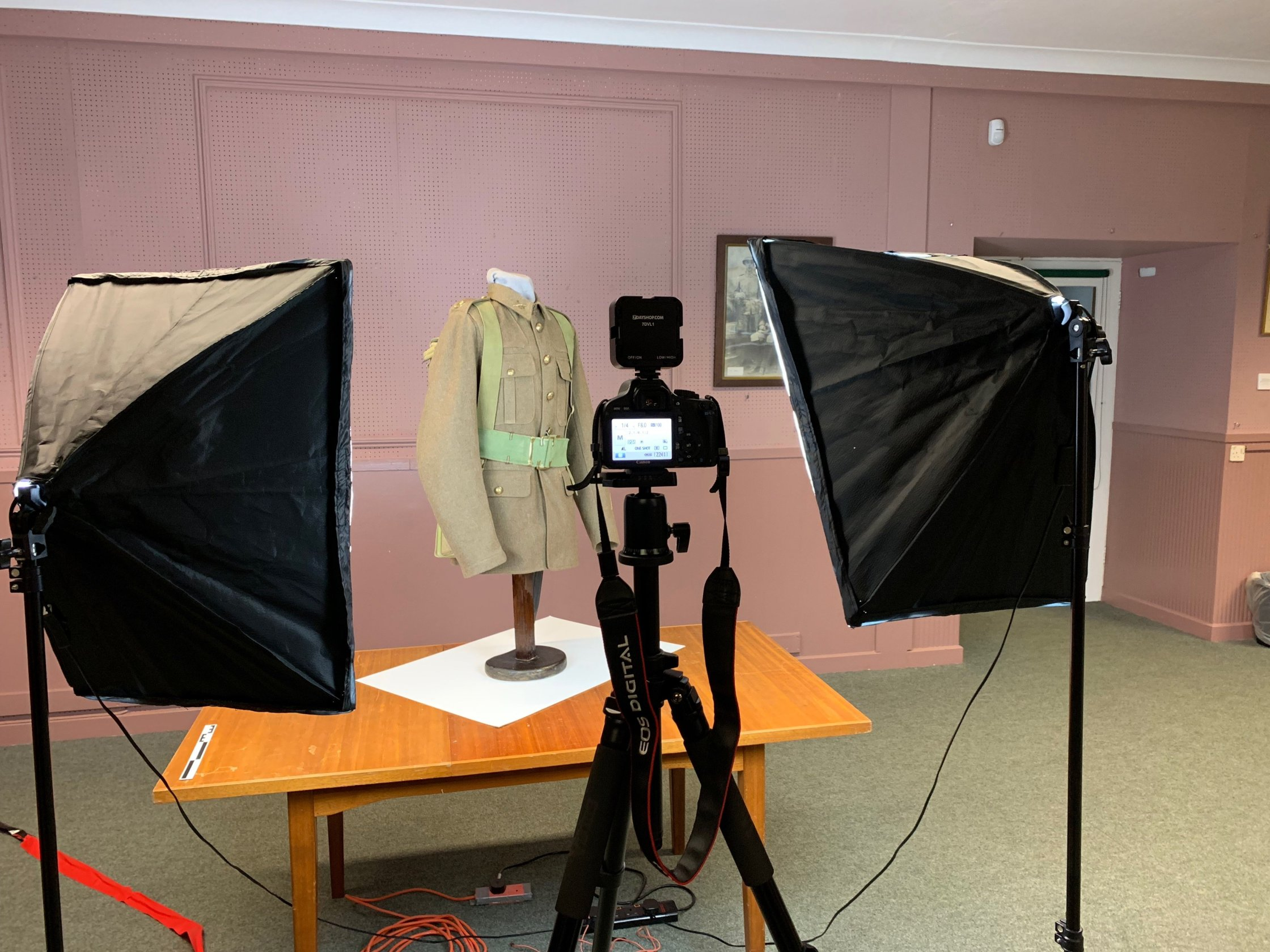 3D scanning a WWI uniform at Cornwall's Regimental Museum. A camera on a tripod points towards a mannequin dressed in the uniform, flanked by two studio lights