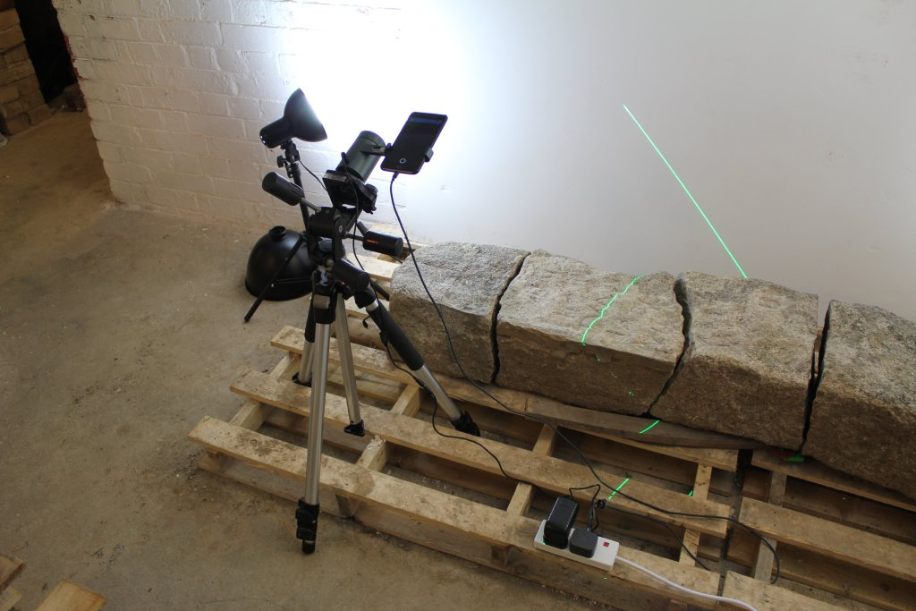 A large stone broken into three pieces lays upon a wooden pallet. On a tripod is a 3D laser scanner, which is capturing the surface of the stone with a green laser stripe which is visible sweeping across the surface of the stone fragments