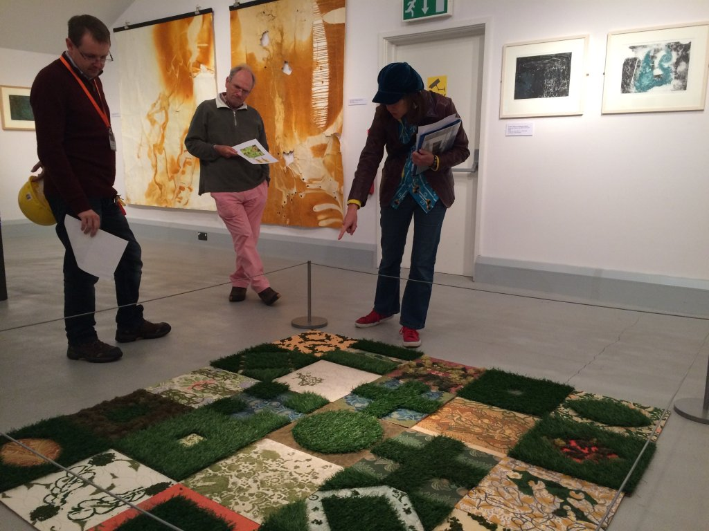 Female artist and two male visitors looking at an exhibit on the floor comprising tiles of turf and abstract patterns from different mining sites.