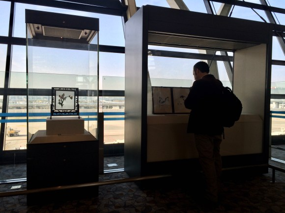 Photograph of man in silhouette looking at two paper exhibits displayed in the glass-clad terminal building of Shanghai Airport, China.