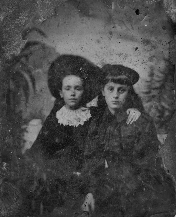 A very old photograph from the 1860s. Two young people, possibly a boy and a girl sitting side by side looking at the camera. They are both wearing hats and mid 19th century clothes.