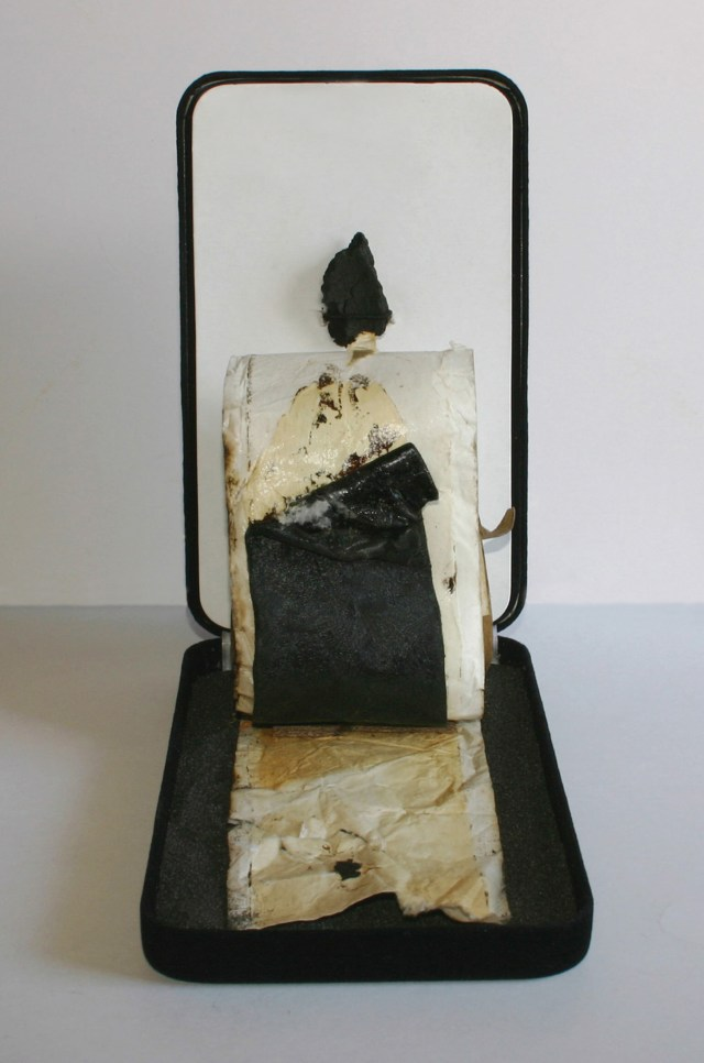 """Black Sand Six""  found object temporary construction - installation  7"" x 4.25"" x 7.625"" ©2011 Gary A. Bibb  (commercial velvet jewelry case, black sand, roofing tar fragment, industrial paper w/ tar)"