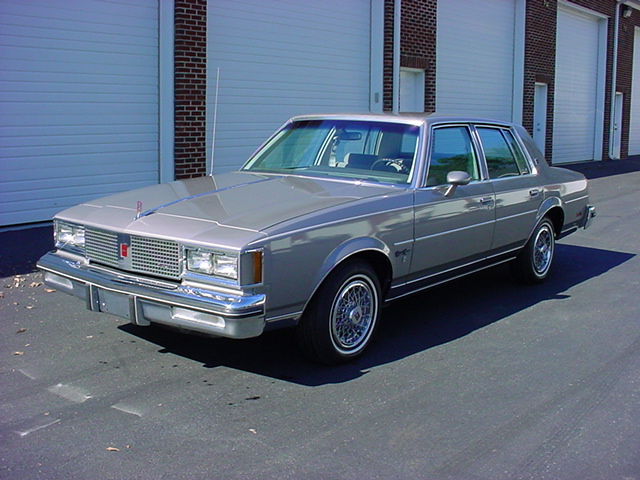 This is not my mother's actual '83 Cutlass Supreme, but looks almost exactly like hers—same color (Silver Sand), loaded, no vinyl top—except mom's had the body-colored Super Sport wheels. It was pretty sharp looking for the time.