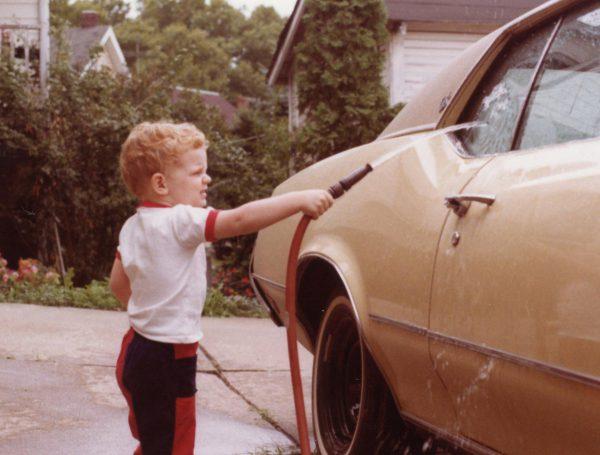 Small child washing a yellow car