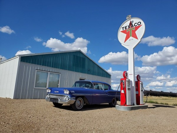 1958 Chevrolet Biscayne in front of gas station.
