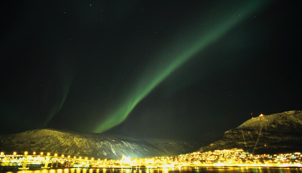 Tromso, Noruega. Aurora boreal sobre as luzes da cidade de Tromso.