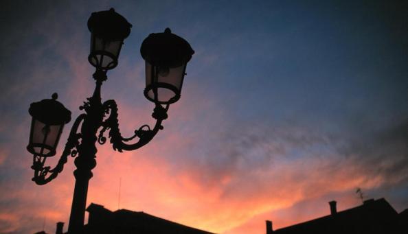 Itália. Silhueta de um poste de rua sob um céu ardente repleto de nuvens escuras.