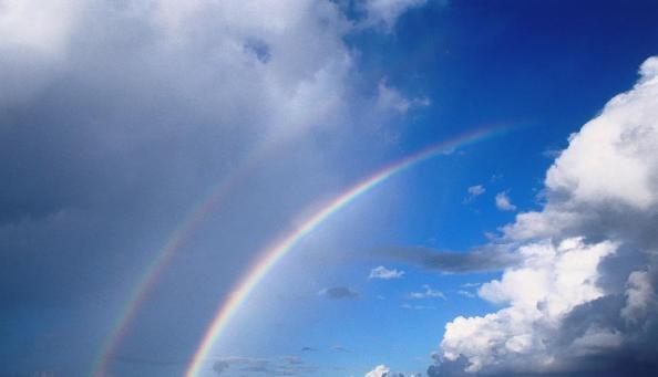 Polinésia Francesa, Rangiroa Tuamotus. Nuvens de tempestade acompanham dois arco-íris sobre o horizonte.