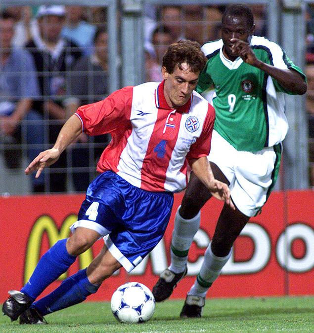 O zagueiro Gamarra, do Paraguai, domina a bola marcado por rival da Nigéria