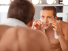 Men appying skin ointment