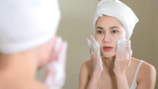 female applying facewash