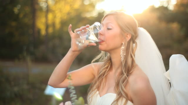 bride in wedding outfit drinking water