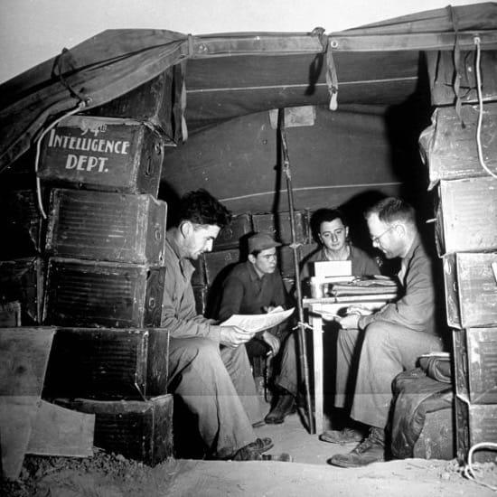 Hombres del departamento de inteligencia, junto con un mecanógrafo, generando el informe de una misión