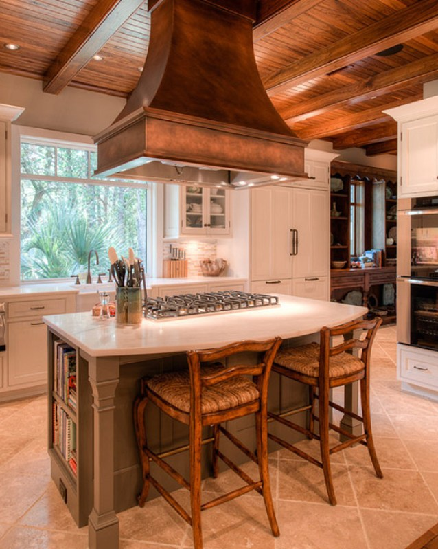 A copper hood accented by a reclaimed wood ceiling and natural stone tiles sets off this country kitchen design. (Source: Home Bunch)