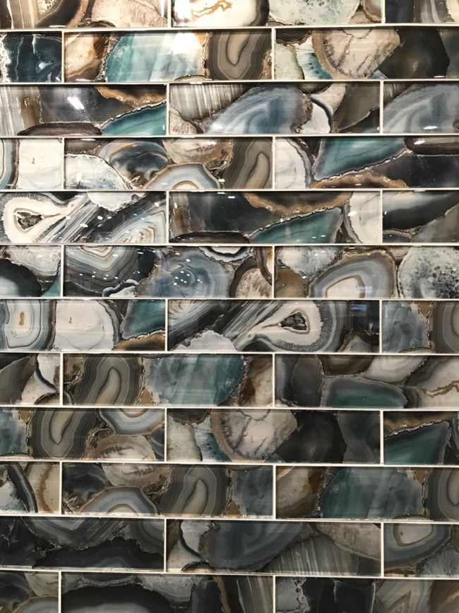 Fluid movement in jaw-dropping colors bring the mystery of geode rocks to vertical surfaces with Glazzio Tiles Magical Forest series.