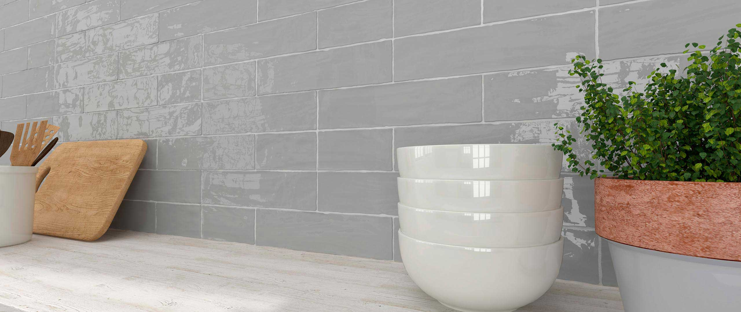 A custom natural cut on a smoky high gloss gray subway tile. Available at Custom Home Interiors