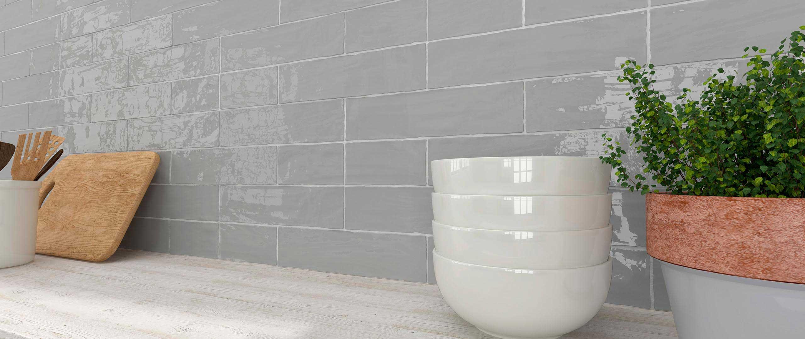 A custom natural cut on a smoky high gloss gray subway tile. Available at Custom Home Interiors