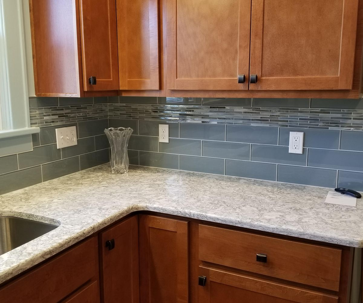 """Glazzio Crystile series glass subway tiles in Gray Sky 4"""" x 12"""" with a border of Lunada Bay Agate Pisa Pearl 1.2"""" x 4"""" brick mosaic"""