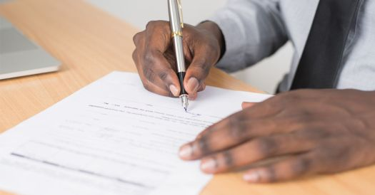 Person Signing a Document on a Wooden Desk with a Silver Fountain Pen