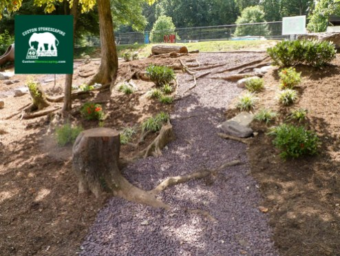 Custom Stonescaping started this project by cutting down a few of the trees that were rotting or needed to be removed. Some of the stumps were left as seating or to play on. The red gravel was added for access so the kids could safely run up and down the hill.