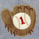 up close picture of leather glove and baseball for 1st birthday