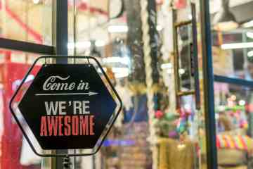 A sign in front of a colorful store reads: Come in, we're awesome