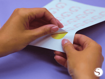 A woman peels a sticker off the page
