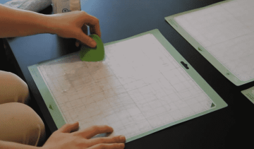 A woman uses a green plastic scraper to to clean a cutting mat.