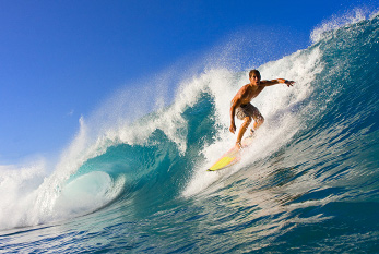 Surfer rides a large blue tropical wave