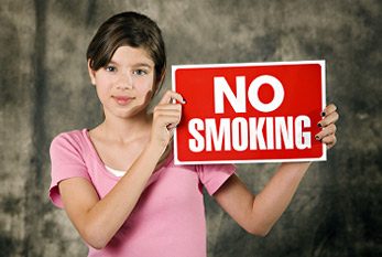 A young girl holds a No Smoking Sign.