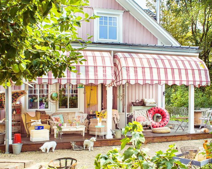 Die Porch/Veranda vom Rosa Haus im Sommer mit Korbmarkise