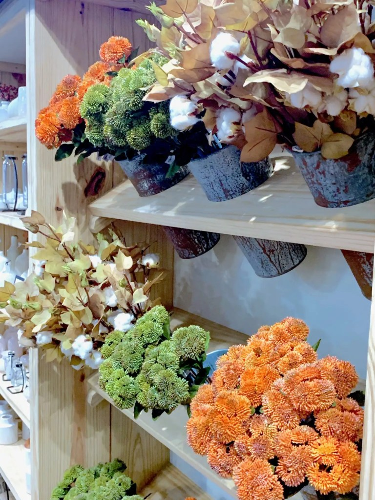 The faux floral department at Magnolia Market includes cotton& peach stems, eucalyptus and green and orange florals.