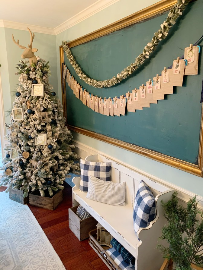Christmas countdown calendar using paper tags, bags and clothespins hung across chalkboard.