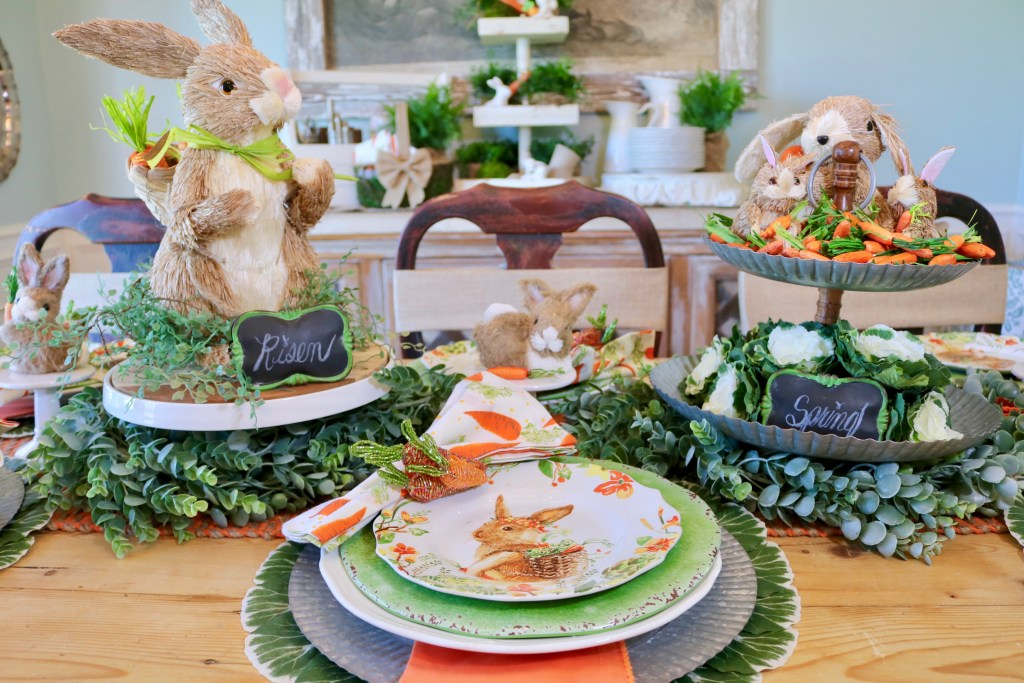 Centerpiece with two tiered tray and decorative bunny on pedestal.